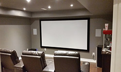 basement entertainment center with large projector screen and leather chairs